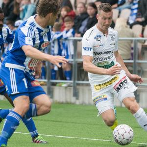 RoPS-backen Juha Pirinen försöker ta sig förbi HJK:s Ville Jalasto och Richard Gadze.