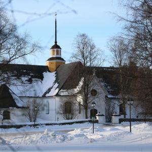 En vit kyrka med svart tak.