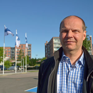 Jarmo Keskitalo poserar, i bakgrunden flaggor.