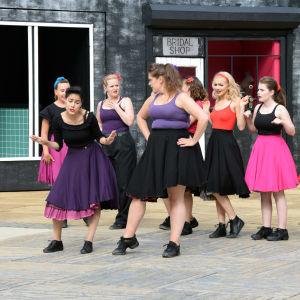 Nio kvinnor på en utescen iklädda femtiotalsklänningar.