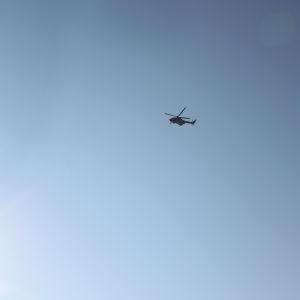 En helikopter flyger på en klarblå himmel