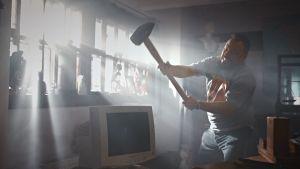 Docventuresin juontaja Riku Rantala rikkoo lekalla tietokoneen näytön.