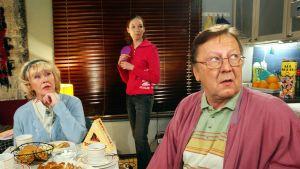 Eeva Litmanen ja Sulevi Peltola istuvat kahvipöydässä. Siiri Sinnemäki seisoo heidän välissään.