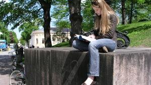 En flicka sitter vid Åbo Domkyrka och studerar.