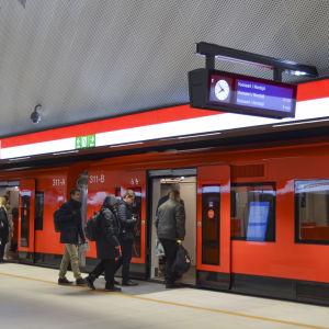 passagerare går in i ett tåg på mattby metrostation på måndag morgon