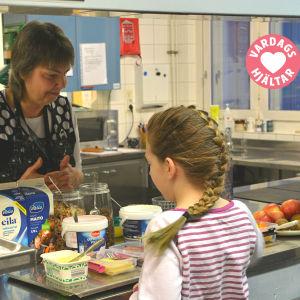 Christel Enholm serverar skolelever i Borgby skola på frukost.