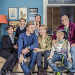 Huvudkaraktärerna i dramaserien Bonusfamiljen samlade i en soffa.