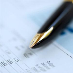 Penna på ett papper med stapeldiagram och siffror.