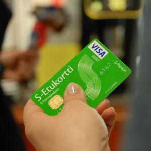 En hand som håller i ett S-bonuskort.