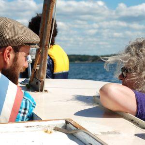 Linus Söderlund diskuterar med Kari-Anne Torstensen på båten från Kasnäs till Brännskär