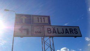 En skylt som visar att Bäljars industriområde (i Karis) är till vänster. Solen skiner, himlen är sommarblå med vita moln.