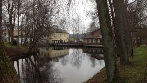 landskapsbild med byggnader invid å.