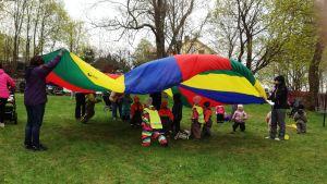 Barn leker under fallskärm.