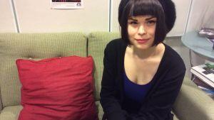 Tummatukkainen nainen istuu sohvalla ja katsoo kameraan hymyillen.