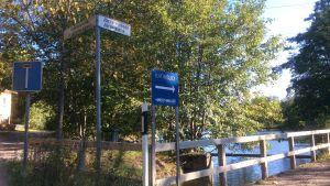 En bro leder över en sjö, gatunamnsskyltar, en skylt som visar vägen till Katinsuo (Kattkärret), trafikmärke för återvändsgränd, soligt höstväder