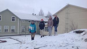 Sami Hämäläinen, Ville Viisteensaari, Fransa Finnilä och Mia Lillhonga står på Vittsar skolas pulkabacke som döljer ett nergrävt hus.