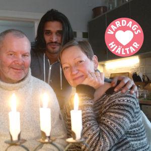 Frank Hellgren, Ahmed Aljuaifari och Pia Rousku poserar bakom en ljusstake med tre tända ljus i familjens kök