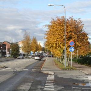 Bilar som kör på huvudgatan i Närpes. Träden vid sidan om vägen är i höstskrud.