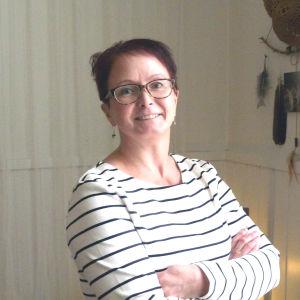 Bild på Camilla Hynynen, står mot en vit vägg