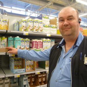 Marketschef Mika Gabrielsson står vid en butikshylla med växtmjölk.