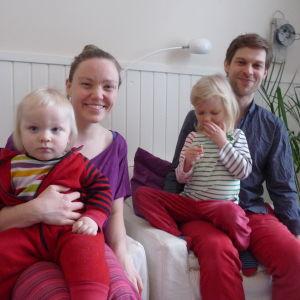 Familjen Lindström-Lindqvist i en soffa. På bild finns föräldrarna Victoria och Jon samt två barn i ålder ett till fyra år.