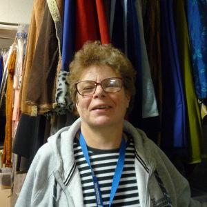 Maggi Ahlfors med en massa kläder i flera rader hängande bakom sig.