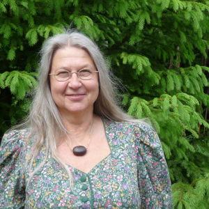 Viveka Grönlund med en stor grön gran bakom sig