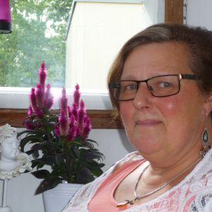 Gun-Britt på balkongen. Lilafärgade och rosa blommor i bakgrunden. En keramikkerub finns också på bordet bakom Gun-Britt.