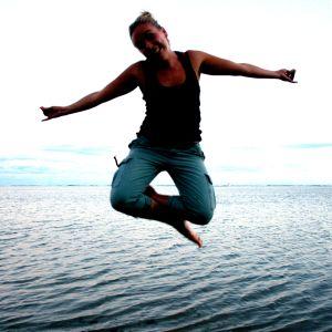 Nainen hyppää, taustalla meri.