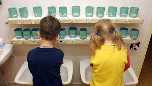 Pika ja tyttö pesevät käsiään päiväkodissa. (2002)