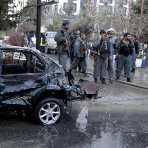 Säkerhetsstyrkor granskar en bil efter en själmordsbombares attack i Kabul.