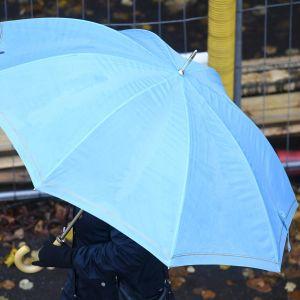 En fotgängare tar skydd undan regnet under ett blått paraply.