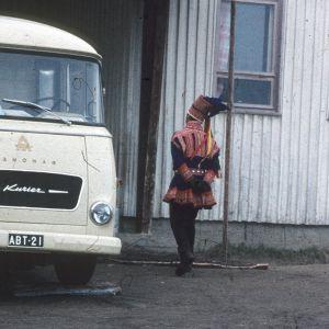 säteilyfysiikan laitoksen mittausauto ja mies Enontekiön mallin lapinpuvussa takaa