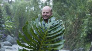 Carl Lingren med ett stort palmblad står med en flod bakom sig