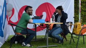 Man och kvinna sitter vid ett bord och sänder radio utomhus.