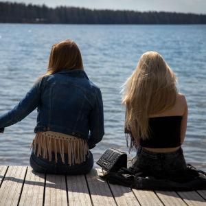 Två tonåriga flickor sitter med ryggen mot kameran på en brygga i sommartid.