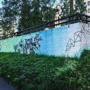 Suojamuuri kadunvarrella, muuriin maalattu sinivihreäsävyinen pöllö