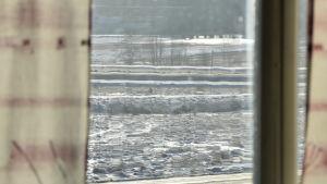 Vy över snöiga åkrar sedd genom ett fönster.