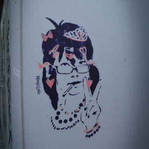 Graffitikonstverk föreställande dam som visar fredstecknet.