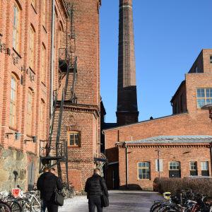 Rödtegelhus vid Vasa universitet. Tre män promenerar över cykelparkering.