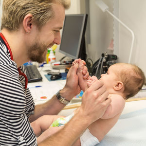 En barnläkare håller upp en baby i hens båda händer.