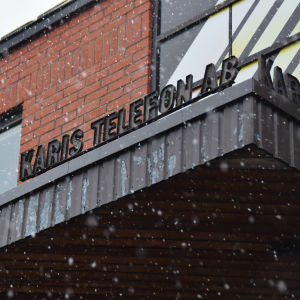 """En bild på ett tegelhus med skylten """"Karis telefon"""" skrivet med svarta bokstäver."""