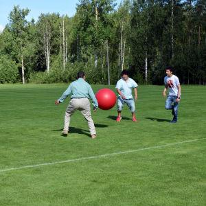 Tre flyktingar spelar med en stor röd boll på en gräsplan i Kisakeskus i Pojo.