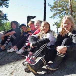 Barn sitter på berg omgivet av sand. Runtomkring dem finns tallar. Barnen heter från vänster Melvin, Victor, William, Selma, Joanna och Fanny.