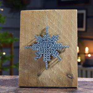 Liten tavla med en bit av planka som botten och skruvar som är skruvade i en form av stjärna på den.