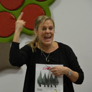 Sandra Westerholm har fingret upp i luften och visar hur tecknet för helikopter ser ut. Sandra är väldigt glad.