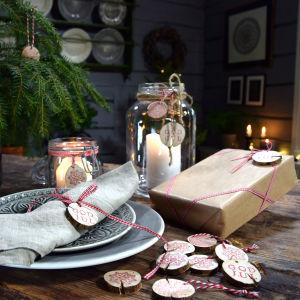 Träornament fast knutna med små band i paket, granen och lycktor som dekoration i Strömsö villan sal.