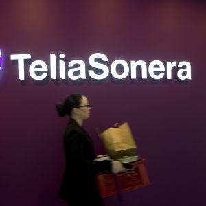 Telia Soneras logotyp mot en vinröd bakgrund. I förgrunden suddigt en kvinna som går förbi.