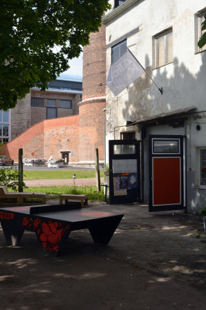 Ett pingisbord framför en rätt så sliten gammal byggnad - ingången till ett museum.