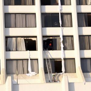 Räddningsarbetare letar igenom hotellet Regent Plaza i Karachi efter branden 5.12.2016